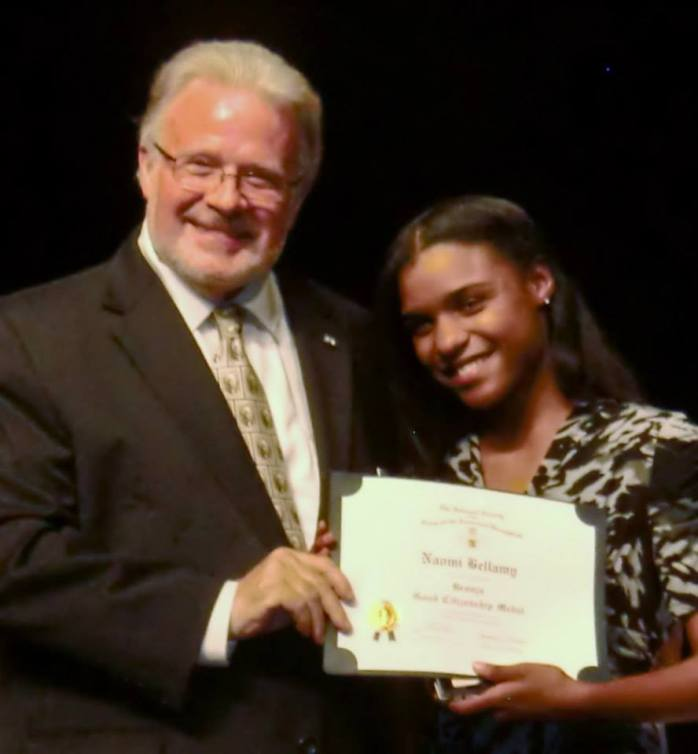 Leah Bellamy receives the award for her sister Naomi from Countryside High School